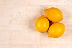 Configuration plate au-dessus des citrons jaunes du fond trois en bois Photo libre de droits