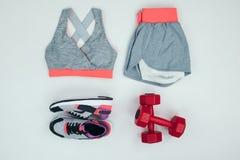 Configuration plate avec des vêtements de sport avec des espadrilles et des haltères Photographie stock libre de droits