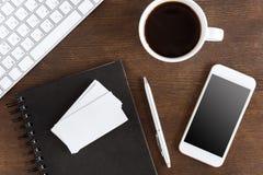Configuration plate avec la tasse de café, les cartes vierges et les appareils sans fil Photographie stock