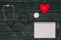 configuration plate avec le coeur rouge disposé, le stéthoscope et le carnet vide sur le dessus de table en bois foncé, santé du  images stock