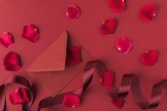 Configuration plate avec les pétales, l'enveloppe et le ruban de roses rouges disposés d'isolement sur le rouge Image stock