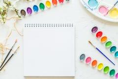 Configuration plate créative des palettes d'aquarelle, pinceaux, livre blanc Lieu de travail d'artiste sur un fond concret gris photographie stock libre de droits