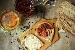 Configuration plate Déjeunez avec le thé noir, la confiture de fraise et le pain frais coupé en tranches avec du beurre sur une s Photos stock