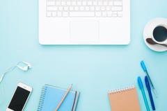 Configuration plate d'espace de travail avec l'ordinateur portable, le smartphone, le café et les papeterie blancs Photographie stock libre de droits