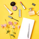 Configuration plate d'espace de travail féminin de bureau avec le journal intime, produits de maquillage, parfum Images stock