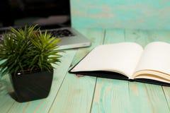 Configuration plate de bureau d'espace de travail avec le carnet de blanc de smartphone d'ordinateur portable et la plante verte Photographie stock