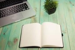 Configuration plate de bureau d'espace de travail avec le carnet de blanc de smartphone d'ordinateur portable et la plante verte Image libre de droits