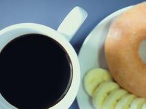 Configuration plate de café noir dans la tasse blanche avec la banane et le beignet franc Photographie stock