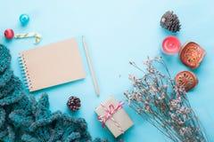 Configuration plate de carnet de métier, d'ornements de Noël et de boîte-cadeau vides sur la couleur en pastel Photos stock