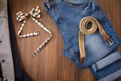 Configuration plate de costume occasionnel, de blues-jean, de ceinture en osier et de b à carreaux Photographie stock libre de droits