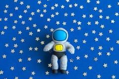 Configuration plate de jouet d'astronaute sur le fond foncé avec des étoiles abstraites image libre de droits