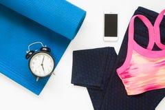 Configuration plate de réveil et de smartphone avec des équipements de yoga Photo stock