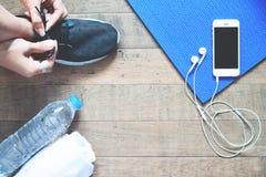 Configuration plate de téléphone portable avec l'écouteur et l'équipement de sport sur le fond en bois Photo libre de droits