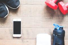 Configuration plate de téléphone portable et d'équipements de sport sur le fond en bois Image stock