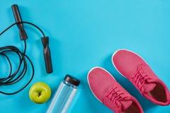 Configuration plate des équipements de sport femelles, corde de saut, bouteille de l'eau et espadrilles roses sur le fond bleu Images libres de droits