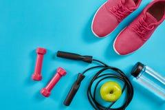 Configuration plate des équipements de sport femelles, corde de saut, bouteille de l'eau et espadrilles roses sur le fond bleu Images stock