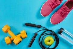 Configuration plate des équipements de sport femelles, corde de saut, bouteille de l'eau et espadrilles roses sur le fond bleu Image stock