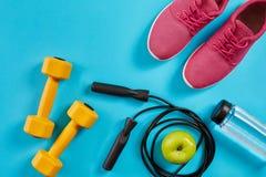 Configuration plate des équipements de sport femelles, corde de saut, bouteille de l'eau et espadrilles roses sur le fond bleu Photographie stock