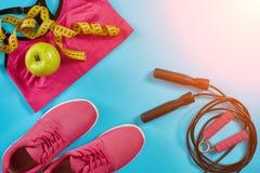 Configuration plate des équipements de sport femelles dans la couleur rose avec la corde de saut et les espadrilles sur le fond b Photo stock