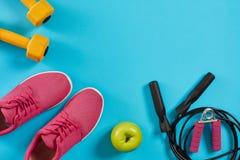 Configuration plate des équipements de sport femelles, de la corde de saut, des haltères et des espadrilles roses sur le fond ble Image libre de droits