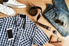 Configuration plate des équipements occasionnels de mode des hommes sur le fond en bois Photographie stock