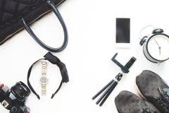 Configuration plate des accessoires de femme avec le téléphone portable et des articles noirs de couleur sur le fond blanc Photo stock