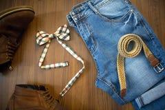 Configuration plate des blues-jean occasionnelles, de la ceinture en osier et du bowtie à carreaux Images stock