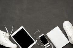 Configuration plate des espadrilles blanches de mode sur le fond noir avec le téléphone, écouteurs, comprimé, livre de copie Images libres de droits