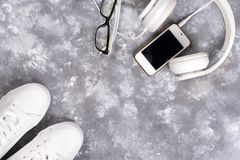 Configuration plate des espadrilles blanches sur le fond en pierre avec le téléphone et les écouteurs Photographie stock libre de droits