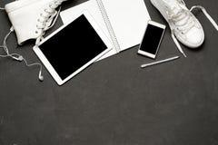 Configuration plate des espadrilles blanches sur le fond noir avec le téléphone, écouteurs, comprimé, livre de copie Photographie stock libre de droits