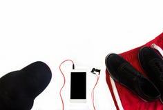 Configuration plate des espadrilles noires et des shorts rouges sur le fond blanc avec le chapeau et le portable Copyspace Concep Photos libres de droits