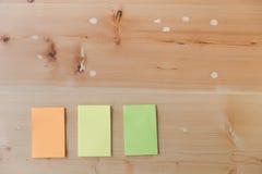 Configuration plate des fournitures de bureau - notes collantes colorées sur la BO en bois Photo stock