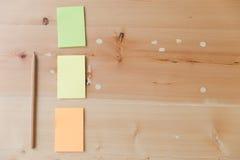 Configuration plate des fournitures de bureau - notes collantes colorées sur la BO en bois Image stock