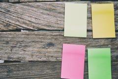 Configuration plate des fournitures de bureau - notes collantes colorées sur la BO en bois Photos stock