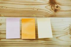 Configuration plate des fournitures de bureau - notes collantes colorées sur la BO en bois Images stock