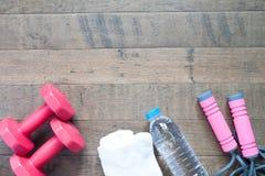 Configuration plate des haltères et de l'équipement de sport rouges sur le fond en bois Photo stock