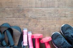 Configuration plate des haltères et de l'équipement de sport rouges sur le fond en bois Photos libres de droits