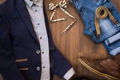 Configuration plate des vêtements sport des hommes réglés et des chaussures sur le Ba en bois brun Image stock