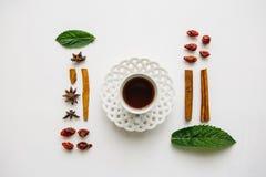 Configuration plate par tasse de thé de fines herbes ou noir parfumé et savoureux sur une surface blanche et de divers ingrédient Images stock
