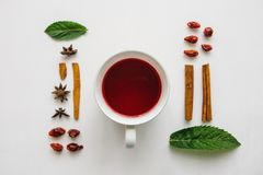 Configuration plate par tasse de thé de fines herbes ou rouge parfumé et savoureux sur une surface blanche et de divers ingrédien Photos stock