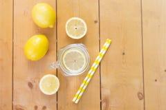Configuration plate Pot en verre de maçon avec l'eau, les citrons frais et les pailles sur la table en bois Frais chaud d'été photo stock