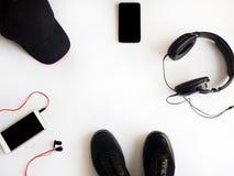 Configuration plate Smartpnones, espadrilles noires, chapeau et écouteurs sur le fond blanc Image stock