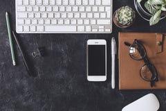 Configuration plate Table foncée de bureau avec le bloc-notes d'ordinateur, souris, stylo, p Image libre de droits