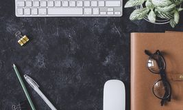 Configuration plate Table foncée de bureau avec le bloc-notes d'ordinateur, souris, stylo, p Photo stock