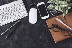 Configuration plate Table foncée de bureau avec le bloc-notes d'ordinateur, souris, stylo, p Image stock