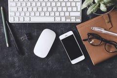 Configuration plate Table foncée de bureau avec le bloc-notes d'ordinateur, souris, stylo, p Photographie stock libre de droits