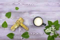 Configuration plate Tasse noire avec du lait Biscuits doux faits maison Brin et fleurs lilas blanches sur la table Images libres de droits