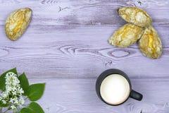 Configuration plate Tasse noire avec du lait Biscuits doux faits maison Brin et fleurs lilas blanches sur la table Photographie stock libre de droits