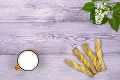 Configuration plate Tasse orange avec du lait Biscuits doux faits maison Brin et fleurs lilas blanches sur la table Photographie stock