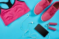 Configuration plate tirée de l'équipement de sport Espadrilles, écouteurs et téléphone sur le fond bleu Image stock